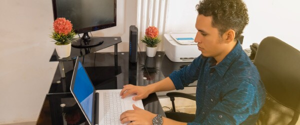 Young Guy Working on Laptop in Home Office