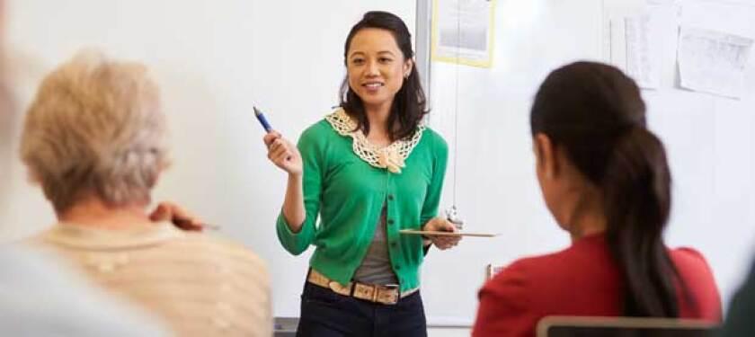 teacher-in-green-shirt-instructing-class-of-adults