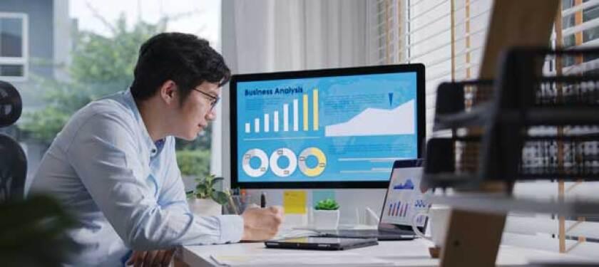 man looking at computer screen of graphs