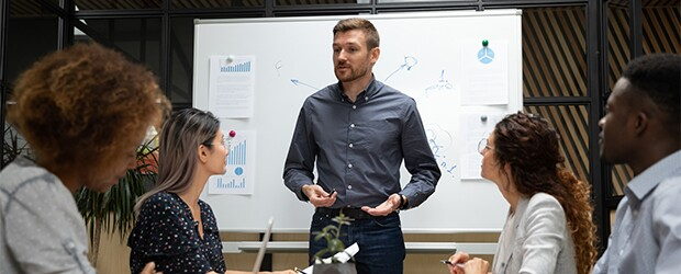 person explaining to 4 others with a blackboard in the background.