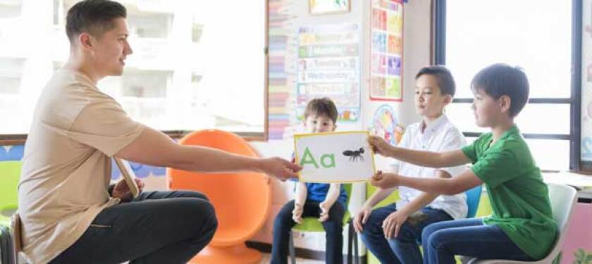 teacher-helping-young-students-learn-the-alphabet