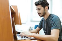 man with dark hair and black beard with headphones on working on computer