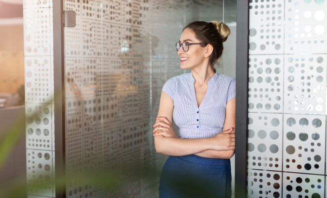 Woman stands inside a glass office looking out to the side