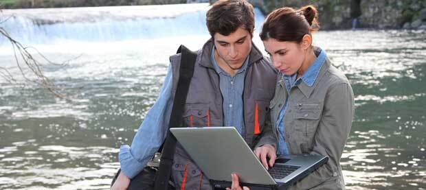 Two scientists stand in front of a body of water, examining a laptop.