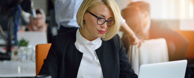 Concentrated businesswoman focused on laptop in office environment