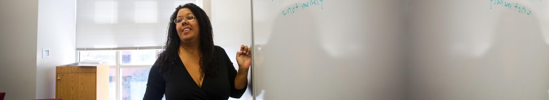 Professor Saru Matambanadzo stands at the whiteboard