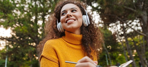woman-in-yellow-turtleneck-wearing-headphones-writing-in-notebook-in-front-of-tree