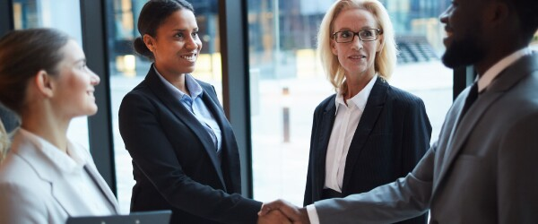 Two people shake hands in a group of diverse professionals