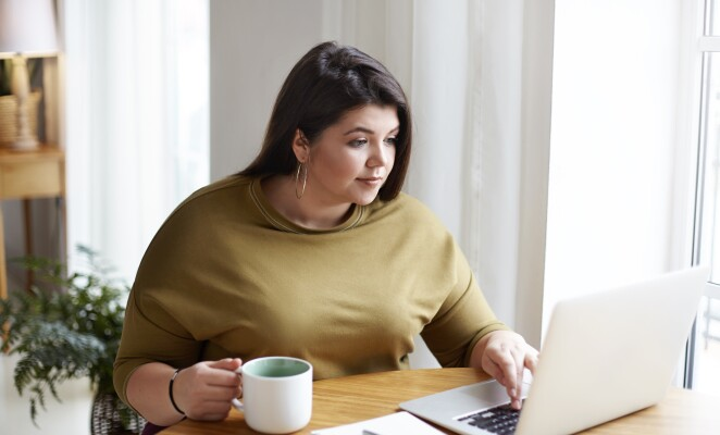 Professional works at desk at home looking at laptop