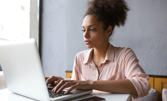 Woman in pink blouse works on computer