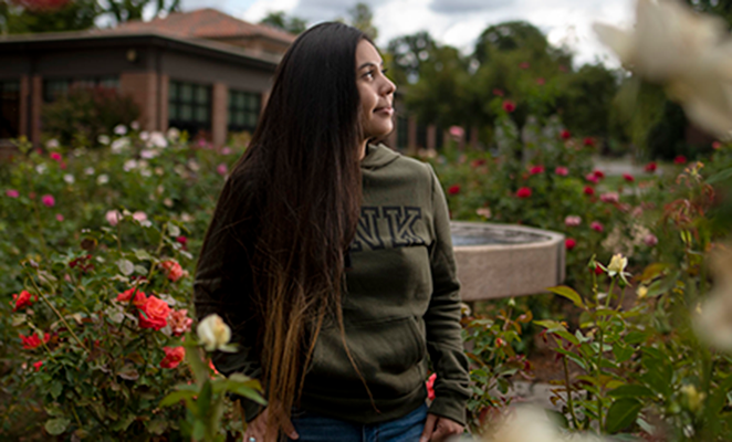 Female Chico State student in campus rose garden
