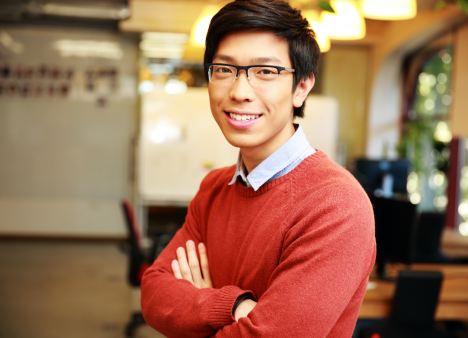 Man in sweater stands confidently with arms folded in office