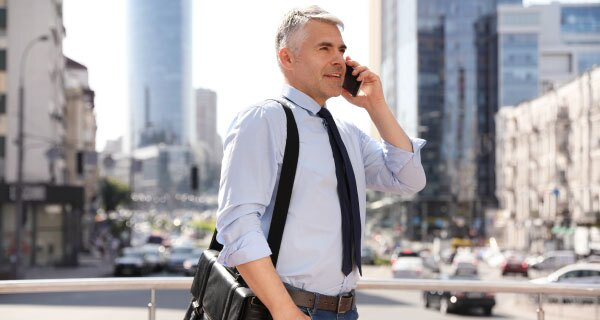 man-in-white-shirt-black-tie-and-pants-carrying-messenger-bag-on-phone-in-city