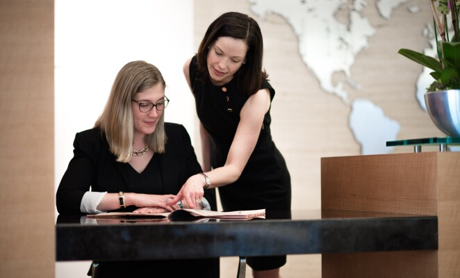 Two women in business attire review materials on a desk