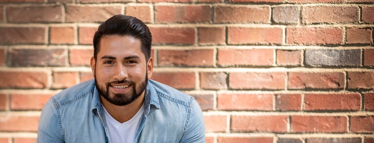 Male Chico State student smiling in front of brick wall on campus