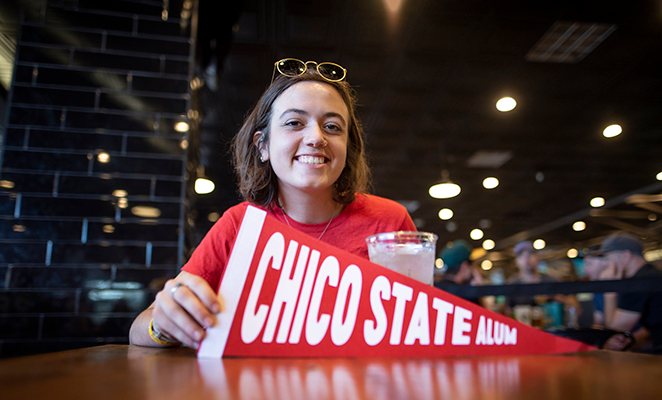 """Female Chico State student with red shirt holding sign that says """"Chico State Alum"""""""