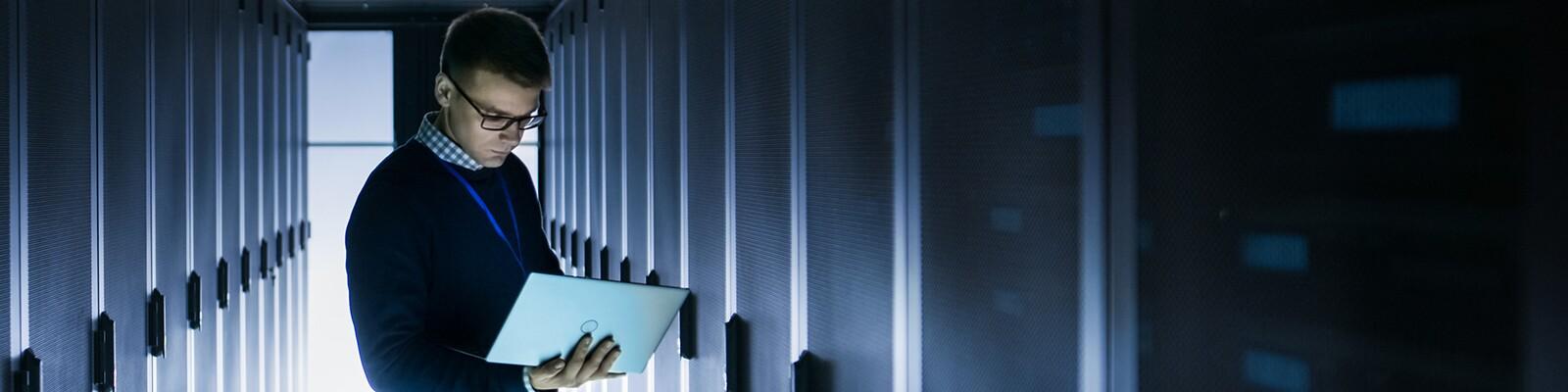 man-on-laptop-in-server-room