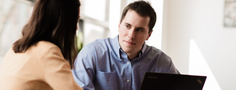 Marquette graduate student speaks to another student in a conference room