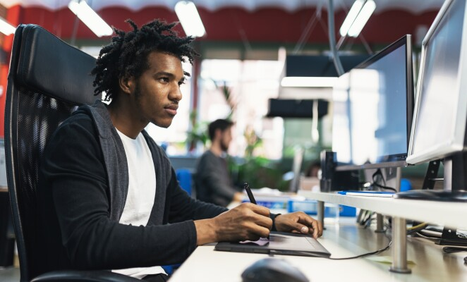 Professional in a black zip up jacket sits at desk working on desktop computer