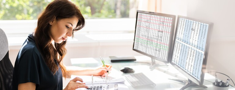 woman-using-calculator-and-computer-at-desk
