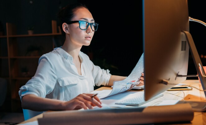 Woman works at night on computer at desk