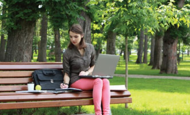 girl sitting on park bench with laptop working