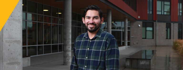 Man wearing plaid button down stands outside in front of a building