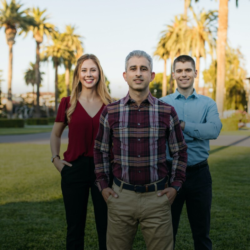 Three Santa Clara University students pose in the grass on campus
