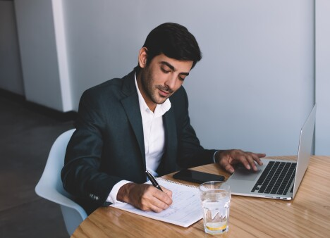 Professional in a suit sits at a table working on laptop