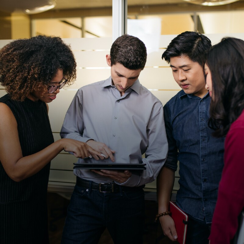 Group of professionals review information on a tablet in the hallway