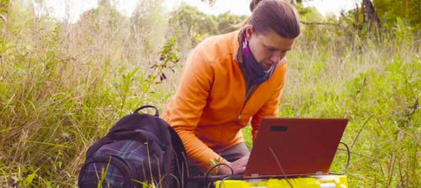 woman in an orange shirt on a laptop outdoors