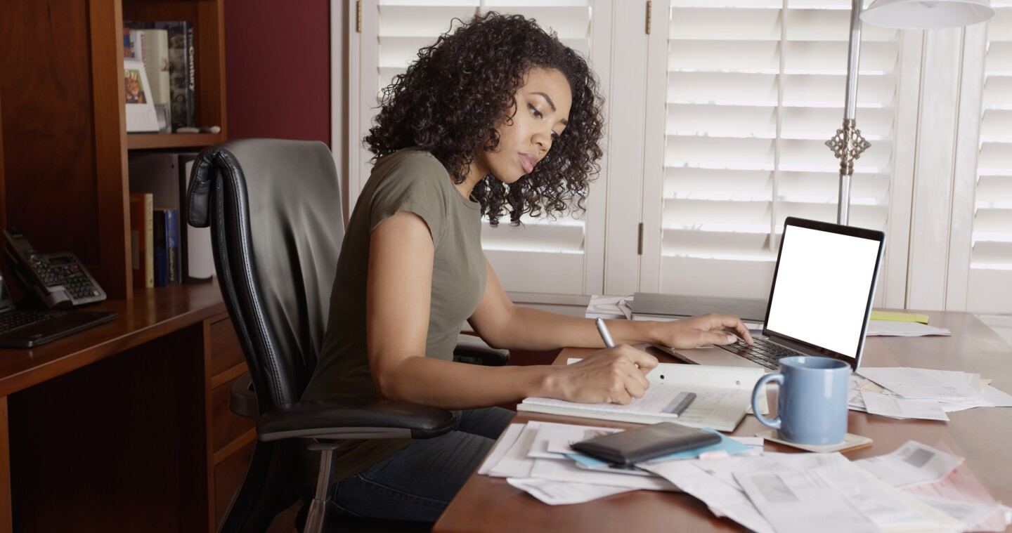 Woman works on paper documents and laptop while sitting in office