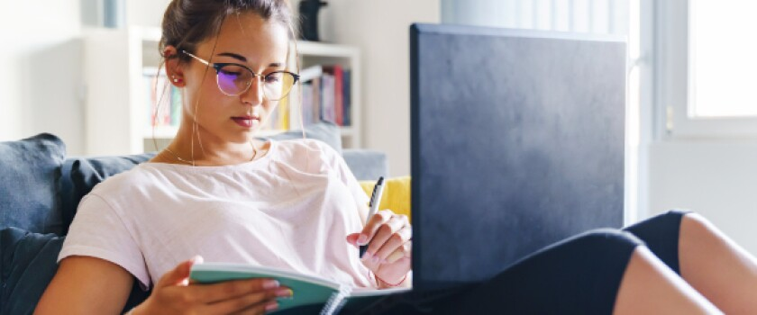 Young woman wearing glasses makes notes in notebook while working with laptop on her lap