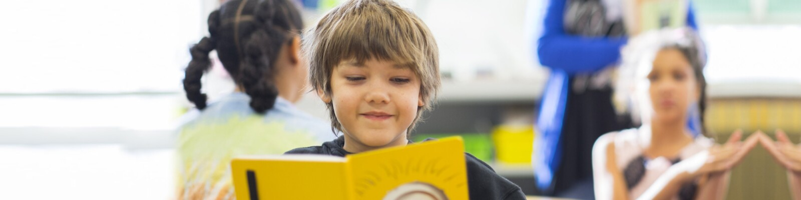 Boy reading a book and smiling