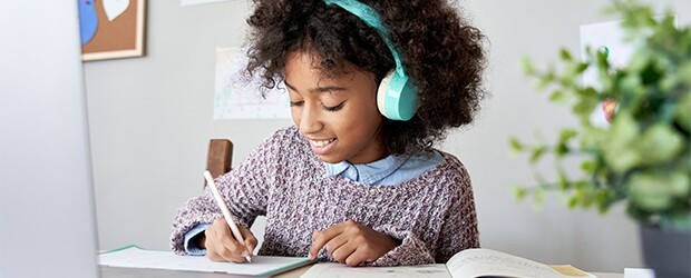 girl-wearing-headphones-writing-on-a-piece-of-paper