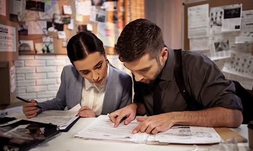 Two-Criminal-Investigators-Review-Case-Notes-At-Desk