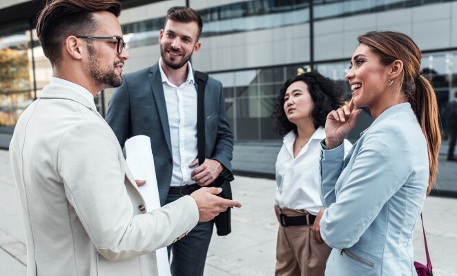 Group of professionals stand outside of a glass building in conversation with one another