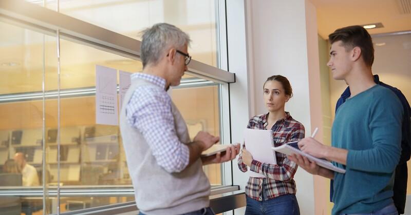 Principal advises student in hallway