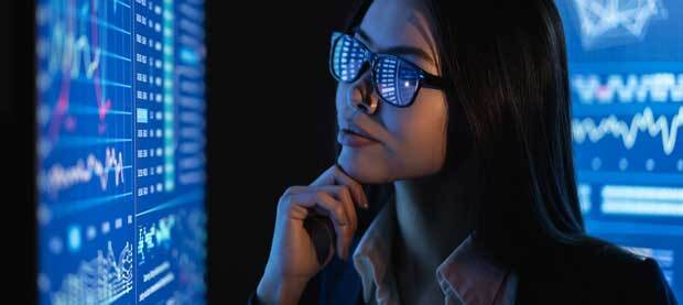 woman with glasses looking at blue screen full of data