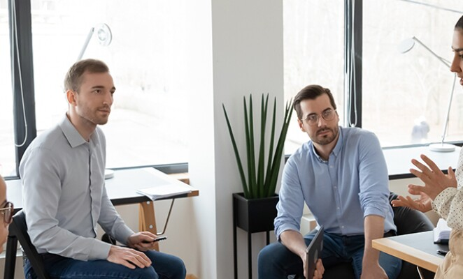 Group of coworkers sit around an office in discussion
