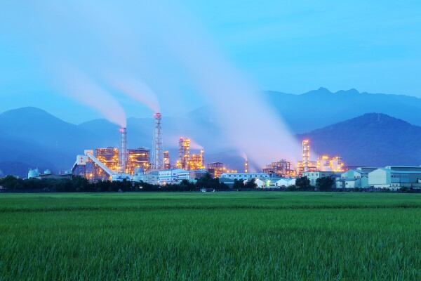 View of a factory in the middle of a green farmland in the early morning twilight ~ Factory pipes polluting air in a silent morning, a serious environmental issue