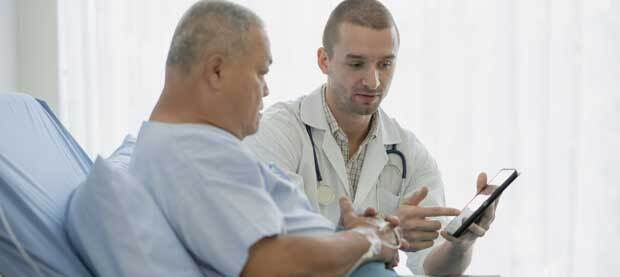 A young male doctor points to the screen of a tablet explaining to an older male patient in a hospital gown what is on the screen.