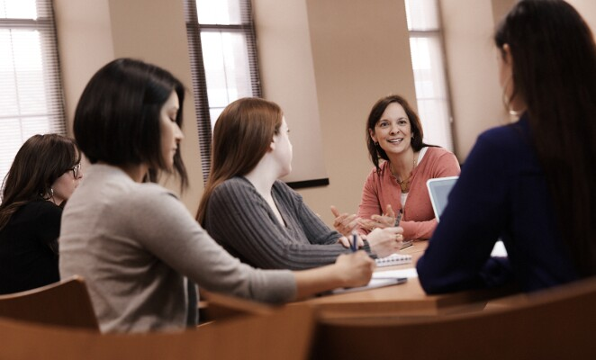 Group of women listen to counselor speaking in the middle of the group