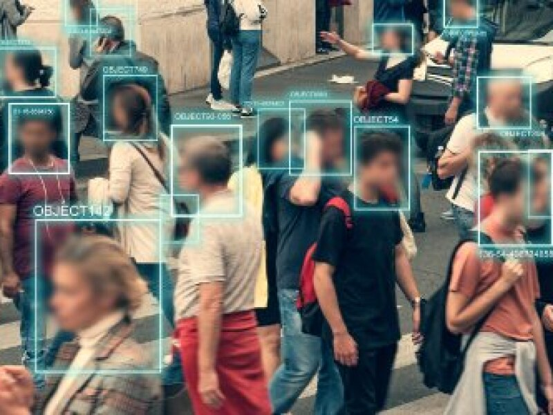 People walking through intersection being digitally face scanned