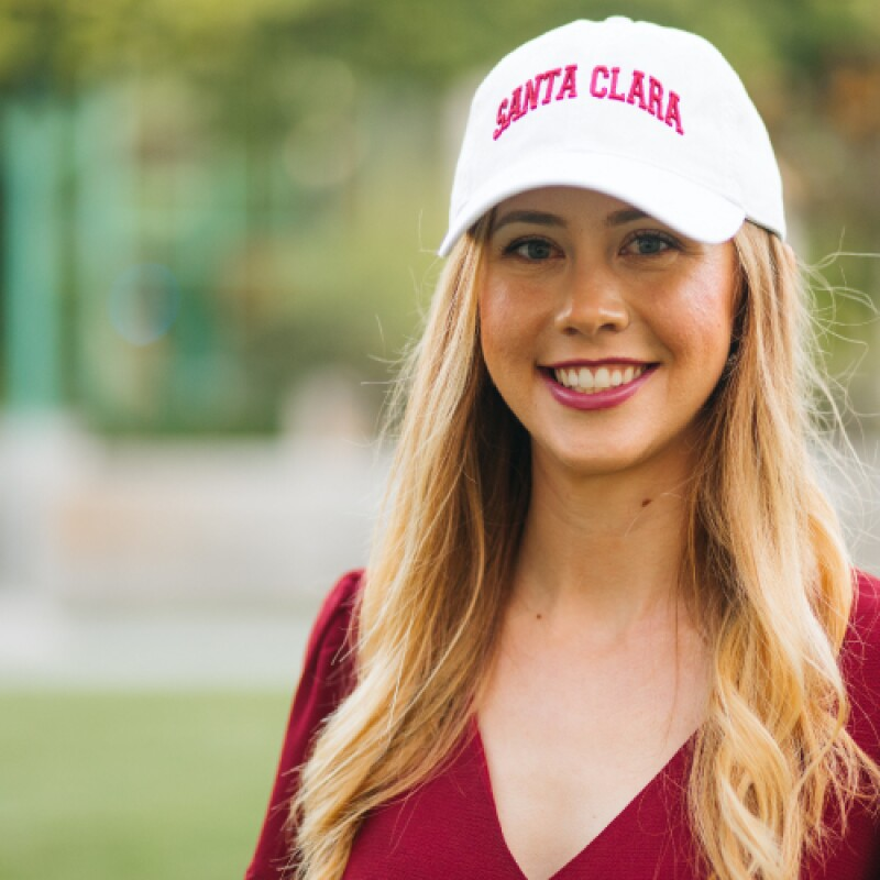 Young female in a red blouse smiles while wearing a white ball cap that reads Santa Clara on it