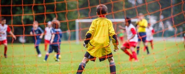 kids-playing-soccer-camera-behind-goalie-in-yellow-orange-net
