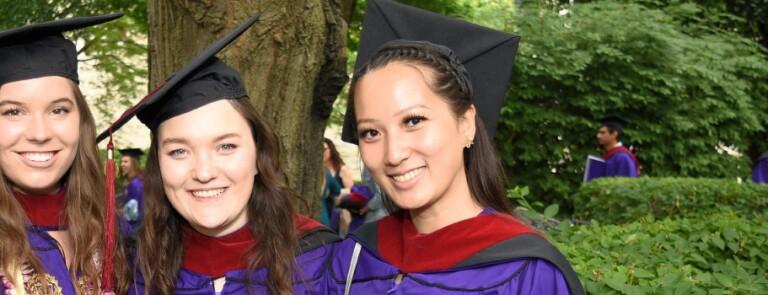 Three IMC graduates smile in their cap and gown