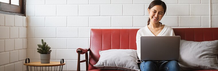 Young professional sits at home on sofa while working on laptop computer