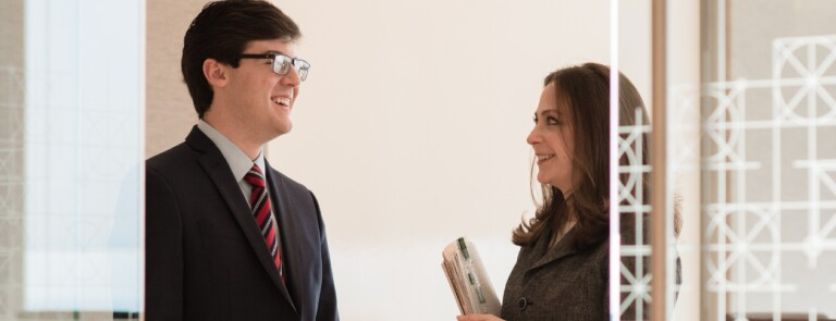Two Marquette students speak to one another in business attire in a glass office space