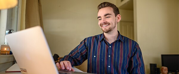 Business student smiling while completing coursework on laptop at home